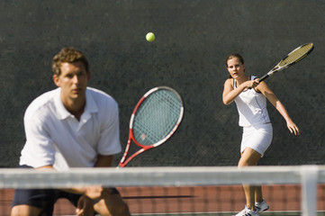 Mixed doubles player hitting tennis ball with partner standing near net