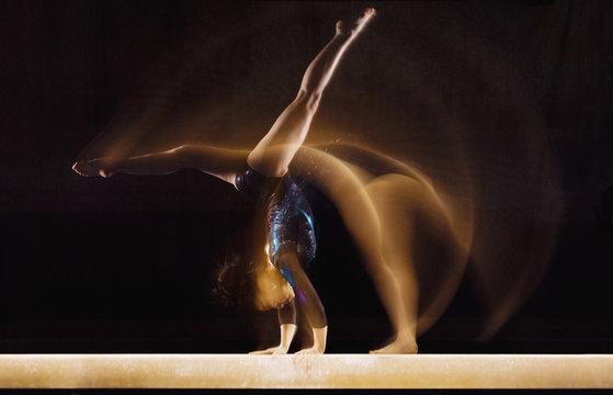 Multiple exposure image of female gymnast in motion on balance beam