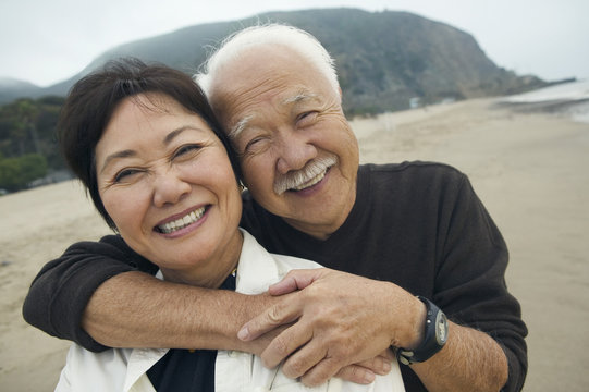 Closeup portrait of a happy senior man embracing woman from behind on the beach