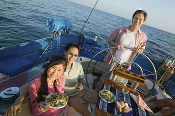 Happy couple having food with friend standing by the steering wheel of the yacht
