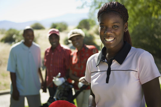 Portrait of happy young African American woman at golf course with people in background