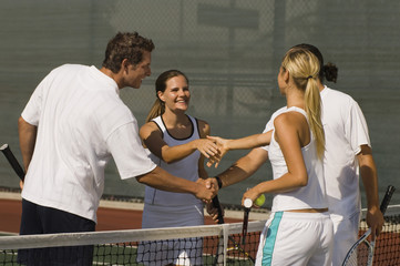 Tennis players shaking hands after match on tennis court