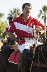 Polo player sitting on horse while holding helmet and polo stick in hand