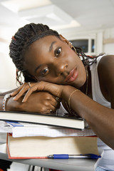 Bored young African American woman resting on stack of books in classroom