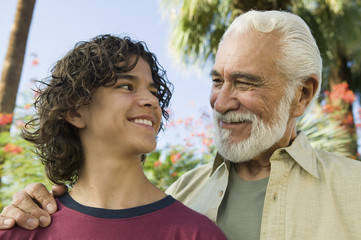 Happy mixed race boy looking at his senior grandfather outdoors