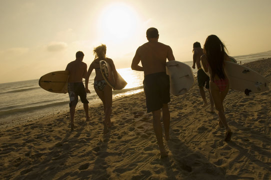 Group of friends with surfboards running towards ocean at sunset