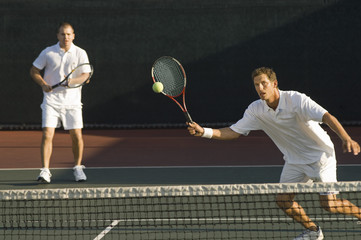 Mixed doubles player hitting tennis ball with partner in the background
