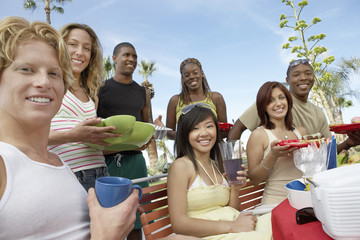 Portrait of happy multiethnic group of friends eating together