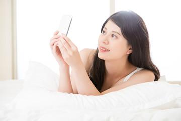 beautiful young asian woman taking selfie by smart phone