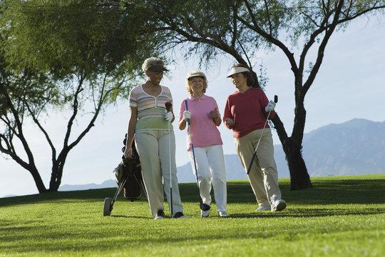 Three mature women walking on golf course