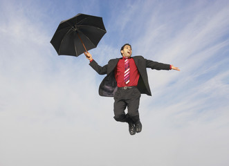 Full length of young businessman flying with umbrella against cloudy sky