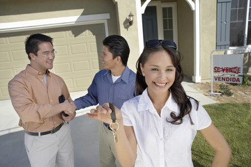 Portrait of young woman holding keys while man shaking hands with agent in background