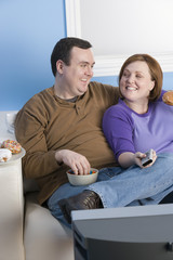 Happy obese couple watching television together at home