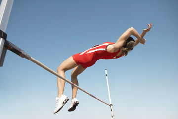 Low angle view of a female high jumper in midair over bar against blue sky