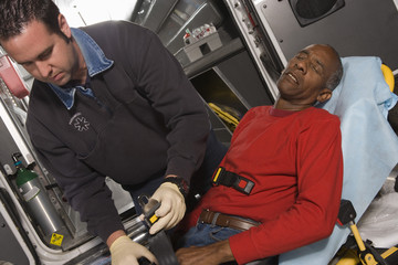 Male EMT professional taking care of a senior man inside ambulance