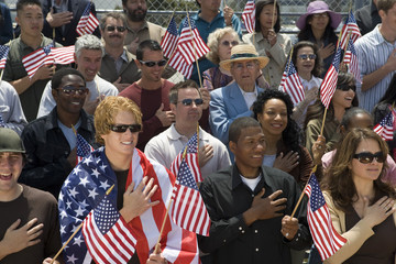 Group of multiethnic people singing American national anthem and holding American flags Fototapete
