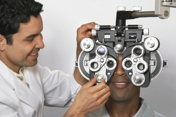 Mature male optometrist adjusting panels of phoropter while examining patient