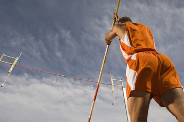 Low angle view of a male pole vaulter preparing for a jump