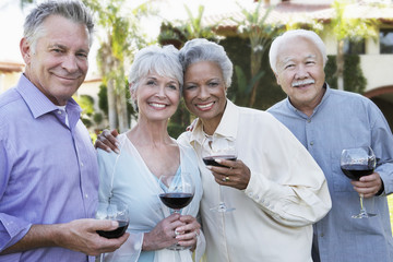 Portrait of happy senior couples standing outside with wine glasses