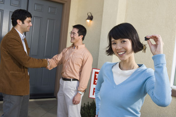 Portrait of happy woman holding house keys with man shaking hands with agent in the background