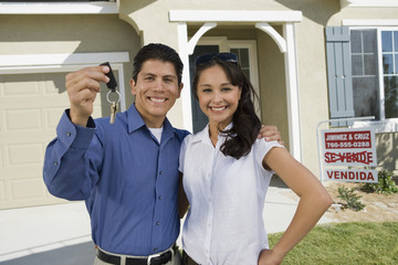 Portrait of happy Hispanic couple holding house keys