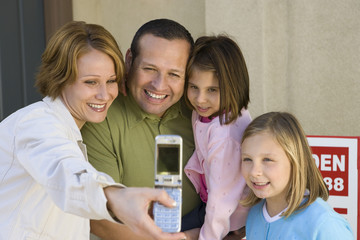 Happy family of four taking self-portrait through cell phone in front of new house