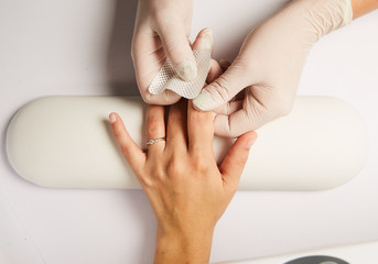 Hands of a doctor applying adhesive bandage on knee   caucasian woman isolated  white background.