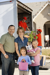 Portrait of a family of four standing in front of a delivery van and house