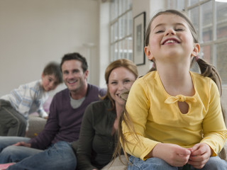 Cheerful little girl with family sitting on sofa at home