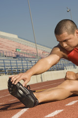 Mature male athlete warming up before starting race
