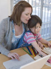 Mother using laptop while daughter coloring book at table in house