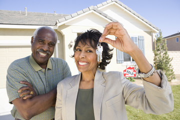 Portrait of happy African American couple with key in front of new house