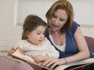 Young woman and cute little daughter looking at picture book in house