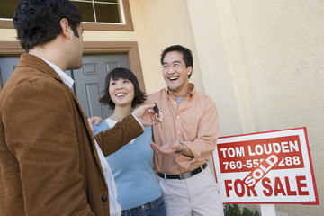 Real estate agent handing house key to happy couple