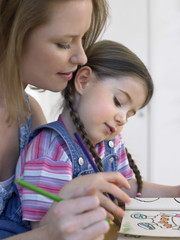 Cute girl and mother coloring book together at home