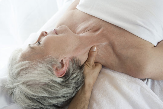 High angle view of a senior woman receiving neck massage at spa