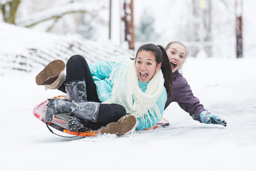 Two young girls sledding down hill in ice and snow