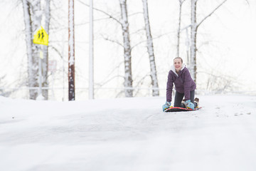 Young girl playing on a snow sled