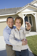 Portrait of happy mature couple holding key in front of new house