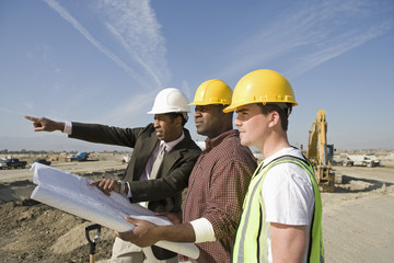 Side view of a surveyor and construction workers in hard hats with plans on site