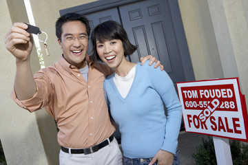 Portrait of happy mature man with woman holding keys of their new home