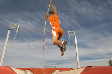 Male athlete pole vaulting against cloudy sky