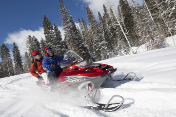 Couple driving snowmobile on snow covered track