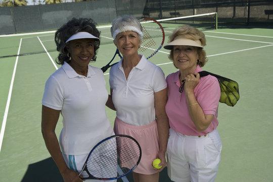 Portrait of diverse senior female friends at tennis court
