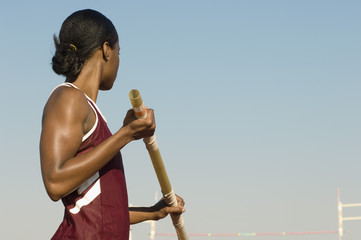 African American female pole vaulter holding pole against clear sky