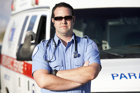 Portrait of a confident male paramedic worker standing in front of an ambulance