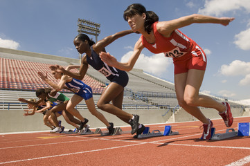 Group of diverse female athletes taking off from starting blocks in race