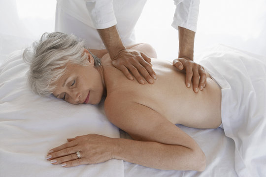 Side view of a senior woman receiving back massage at spa