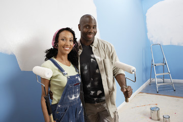 Portrait of happy African American couple painting their new house