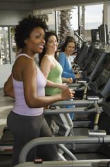 Keuken foto achterwand Fitness Portrait of happy multi ethnic women working out on treadmill in gym